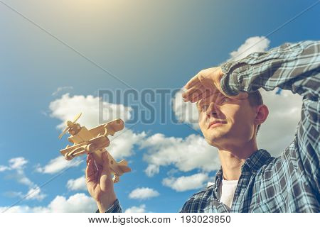 Young handsome man holding wooden toy airplane in hand and looking into the distance at blue sky with clouds background. Dreamer, romantic and creator concept, copy space