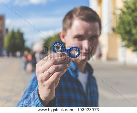 Young hipster man showing to camera fidget spinner, focus on spinner