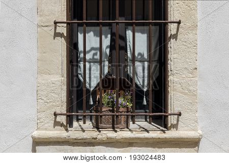Stone french window with old box of violets on windowsill white curtains rusty iron bars