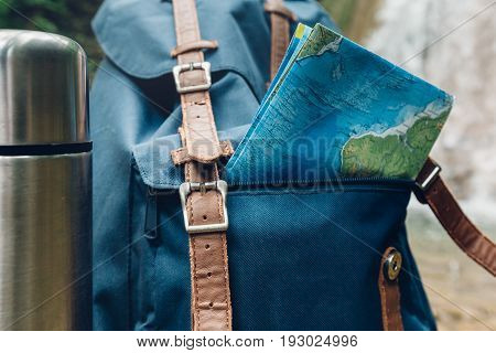 Hipster Blue Backpack Map And Thermos Closeup. View From Front Tourist Traveler Bag On Waterfall Background. Journey Adventure Hiking Concept