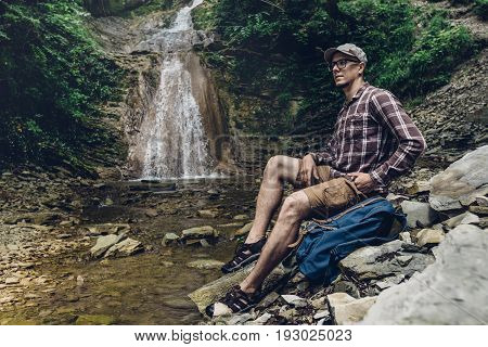 Traveler Explorer With Backpack Sits On The River And Enjoys Surrounding View Exploring Adventure Hiking Concept