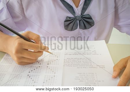 Asian student testing english exam or exercise on exams answer sheets with pencil in class room at uniform school Thai education concept