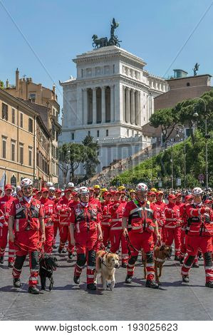 ROME ITALY - JUNE 2 2017: Italian Red Cross troops with dogs trained for rescue missions participating at the parade of national day of Italy. The Monument a Vittorio Emanuele II in background.