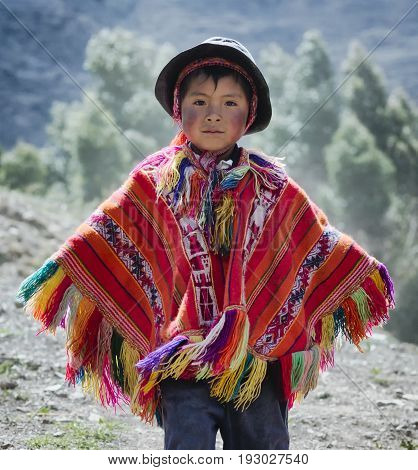 Peruvian boy dressed in colourful traditional handmade outfit. October 21 2012 - Patachancha, Cuzco, Peru