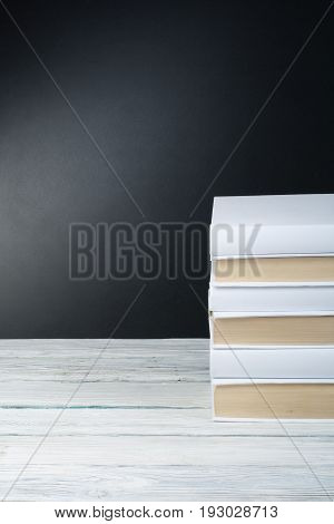 Open black and Whitel books on wooden table, black board background. Back to school. Education business concept
