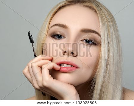 Young Blonde Woman Holding Brow Brush