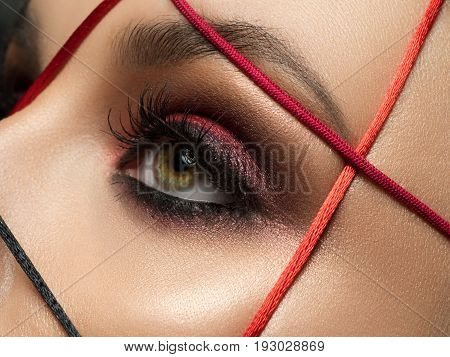 Close up fashion portrait of young beautiful woman with modern trendy makeup. Dark red smokey eyes. Studio shot.