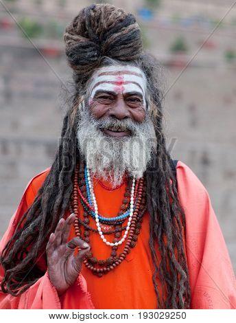 VARANASI, INDIA - JANUARY 3, 2016: Sadhu (Holy man) seeking alms at Dasashvamedh Ghat.