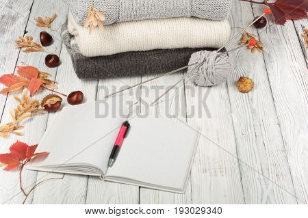 Knitted wool sweaters. Pile of knitted winter, autumn clothes on wooden background, sweaters, knitwear, pen, book, space for text