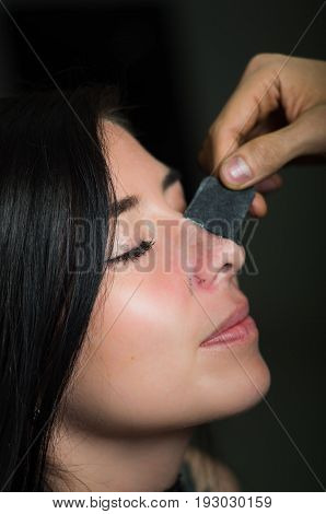 Beauty young woman taking off a black nose mask to clean skin from black spots.