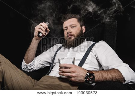 Stylish Man In White Shirt And Suspenders Vaping And Holding Whisky Glass, Isolated On Black