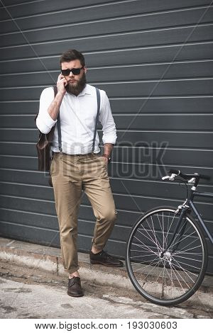 Stylish Man In Sunglasses And Suspenders Using Smartphone And Standing Near Bike