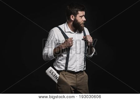 Fashionable Man In White Shirt And Suspenders Standing With Business Newspaper In Pocket Isolated On