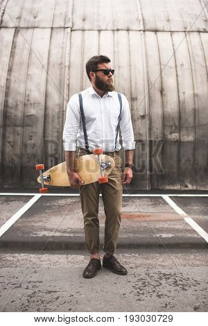 Stylish Bearded Man In White Shirt And Suspenders Holding Longboard On Parking Place