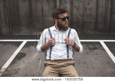 Stylish Bearded Man In Sunglasses And Suspenders Sitting On Parking And Looking Away