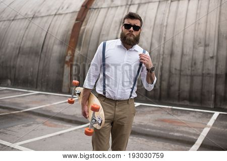 Stylish Bearded Man In Sunglasses And Suspenders Holding Longboard On Parking Place