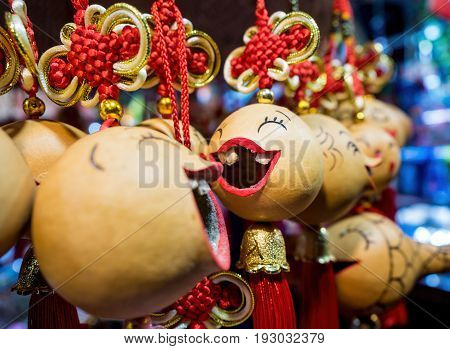 Shanghai, China - Nov 4, 2016: Close-up, shallow depth-of-field view of some hanging souvenir trinkets from a street stall. These objects are attached to tassels in Chinese design style. Low-light image.