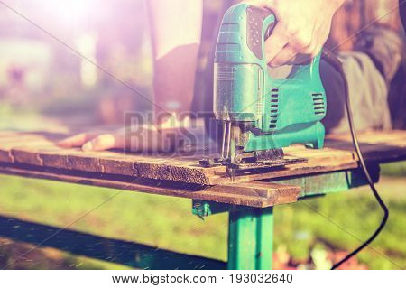 Photo of man working with electric jigsaw in summer on street