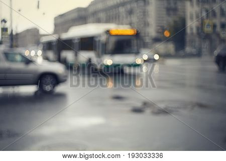 Blurry unfocused background with the urban road with transport in twilight after a rain. Out of focus city landscape with the intersection.
