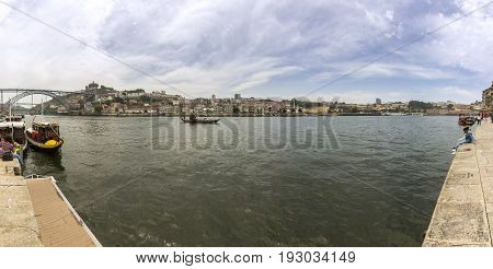Panoramic view from old downtown to Gaia margin Porto Ribeira cityscape and tradicional Rabelo boats on a summer day Portugal.