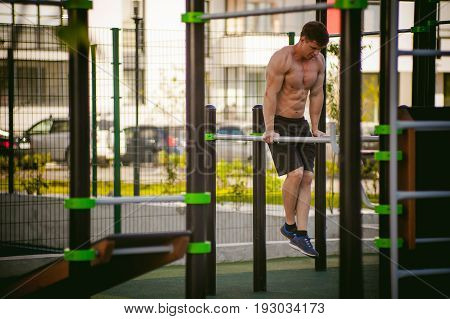 Handsome Sexy Male Bodybuilder Athlete Man Doing Crossfit Workout In Athletic Facilities On Sunny Mo