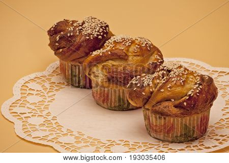 Three cupcakes with cinnamon and sesame seeds on a lace napkin
