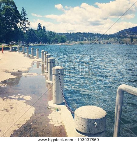 Concrete pillars along flooded lake shore with water on cement path. Summer day. Kelowna. British Columbia Canada.