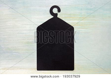 A photo of a blank black business card or price tag in the form of a hanger with a coat, with a place for text, a template for a fashion-related design