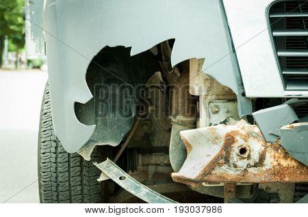 Van broken front plastic bumper with rusty metal reinforcement damaged in car crash accident. Close up. Selective focus.