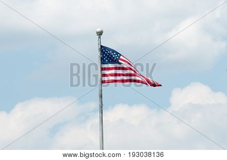 View of Flag of the United States of America with blue sky and clouds behind it