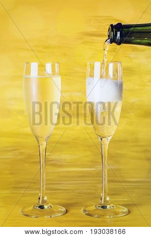 Champagne being poured into glasses from a bottle, against a blurred golden background, with a place for text