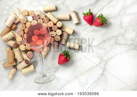 A high-key overhead photo of a glass of rose wine with corks and a fresh strawberries, on a white marble texture with a place for text