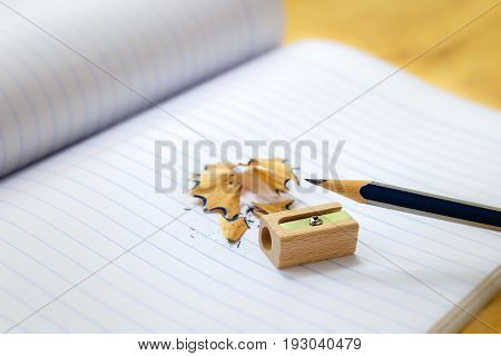 Close-up of pencil sharpener and shavings on note paper.