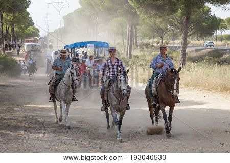 El Rocio Spain - June 1 2017: Pilgrims on horseback in traditional spanish dress on the road to El Rocio during the pilgrimage Romeria 2017. Province of Huelva Almonte Andalusia Spain