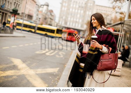 Young Woman Hailing A Taxi On The Street In The City