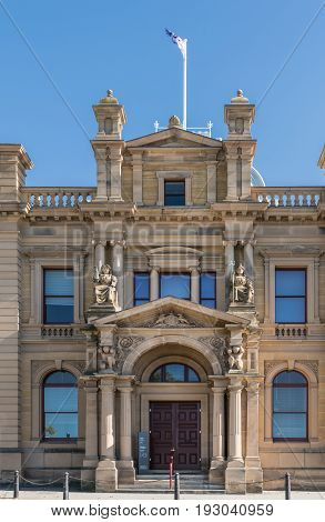Hobart Australia - March 19. 2017: Tasmania. Beige stone Old Custom House converted into Tasman Museum and Art Gallery. Center of facade with monumental entrance. Flag on top with blue sky.