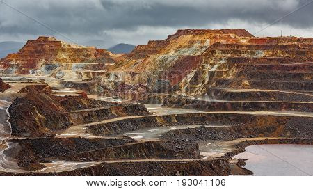 Detailed view of copper mine open pit in Rio Tinto with stormy clouds, Spain