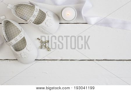 Christening background with white baby booties crystal cross and satin ribbon isolated on white plank floor