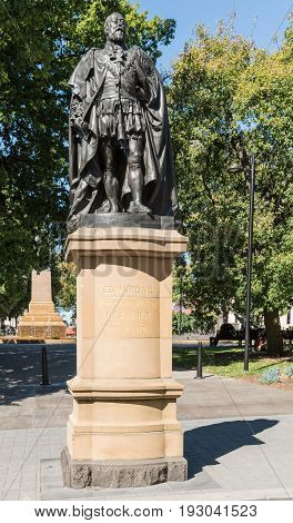 Hobart Australia - March 19. 2017: Tasmania. Bronze statue on stone pedestal of King Edward VII shows him looking proudly and defiant. Green park background.