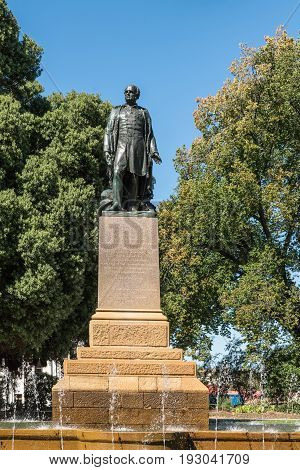 Hobart Australia - March 19. 2017: Tasmania. Bronze statue of Rear Admiral Sir John Franklin shows him looking proudly. Green park background with fountain and blue sky.