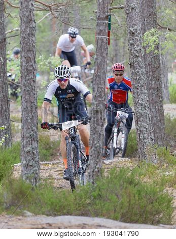 STOCKHOLM SWEDEN - JUNE 11 2017: Group of male mountain bike cyclists in the forest partly hidden of trees at Lida Loop Mountain bike Race. June 11 2017 in Stockholm Sweden