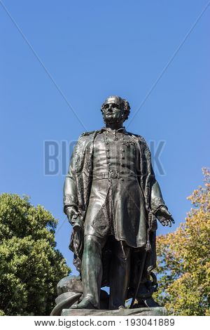 Hobart Australia - March 19. 2017: Tasmania. Closeup of bronze statue of Rear Admiral Sir John Franklin shows him looking proudly. Green park background with fountain and blue sky.