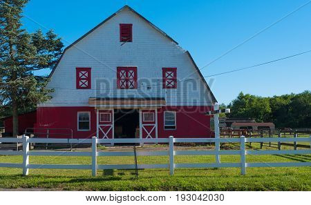 Wall Township NJ USA -- June 26 2017 A red and white barn behind a white picket fence on the Allaire Community Farm. Editorial Use Only.