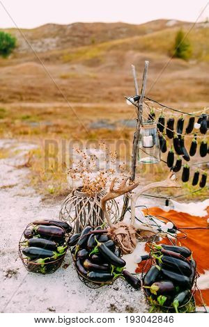 Aubergines lie in iron baskets outdoors near the wooden decor. Wedding decoration