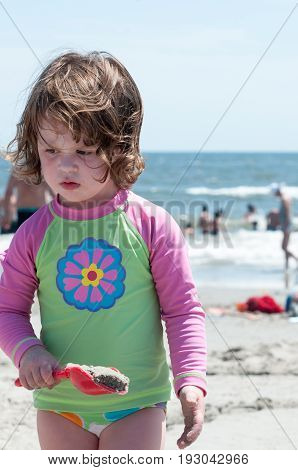 View of Young little girl playing with the sand and building sandcastle at the beach near the sea.