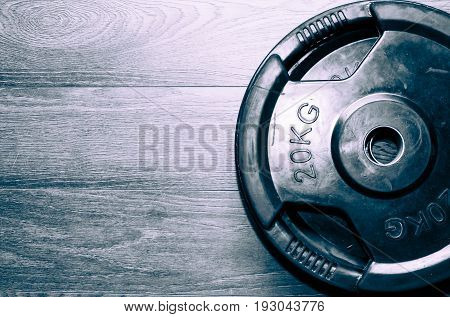 Weight. Fitness exercise equipment barbell weights plate on the gym floor.