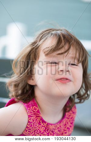 view of squinting expression little girl sitting down making funny face