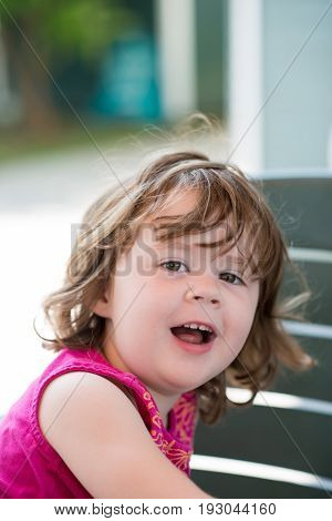 view of young little girl sitting down and looking happy