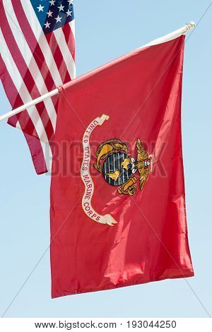 View of United States Marine Corps flag waving on blue sky background, close up, with American flag in background