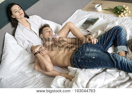 Beautiful couple on the bed. Topless guy in blue jeans lies between the legs of his girlfriend in a white shirt. She holds her hands on his torso and looks forward. Horizontal.